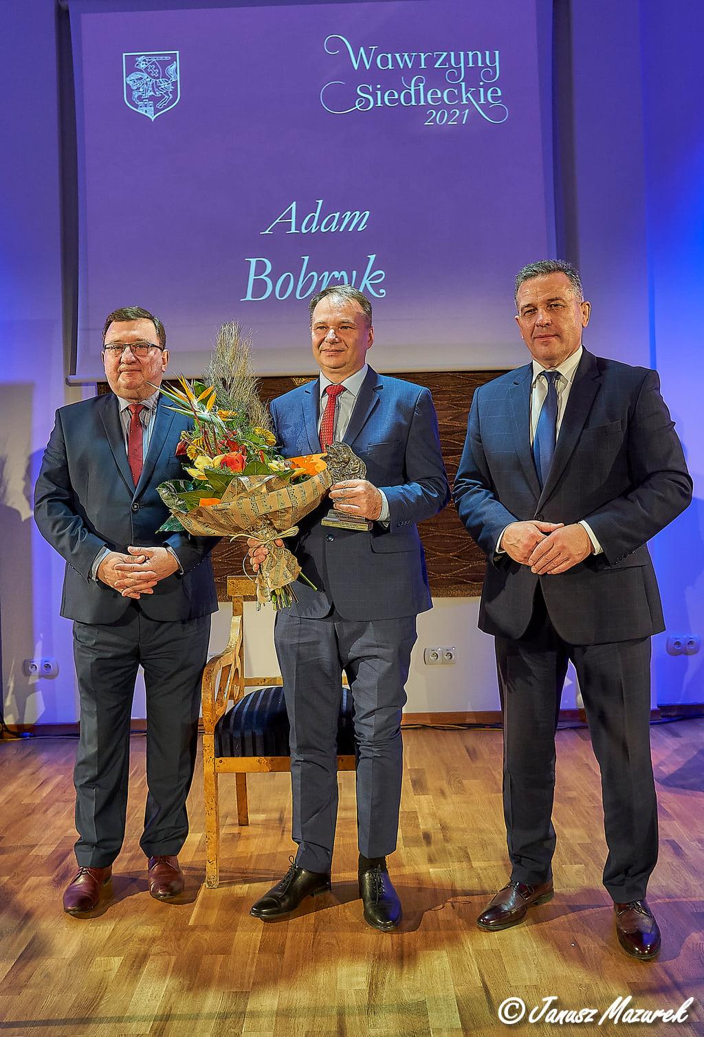 Postać profesora Adama Bobryka oraz osoby wręczające nagrodę